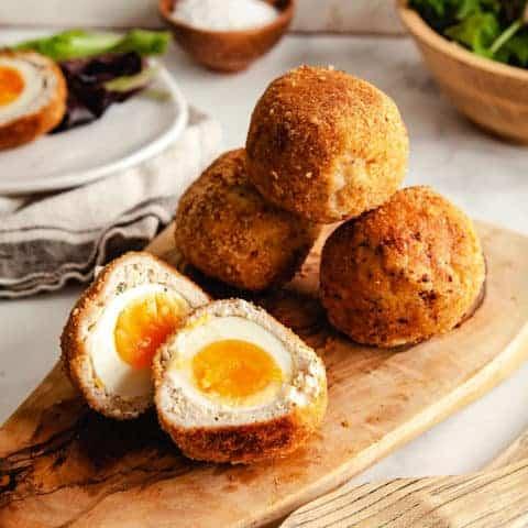 4 Scotch eggs on a wooden platter