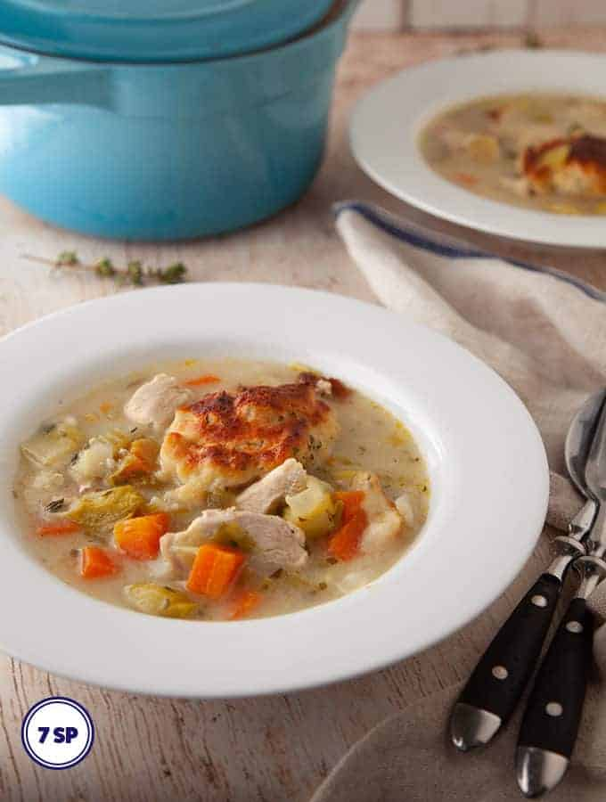 A bowl of easy chicken and dumplings on a wooden board