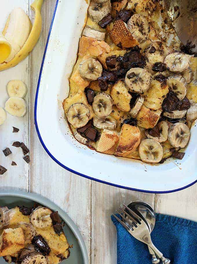 A dish of Bread pudding with banana and chocolate on a white table