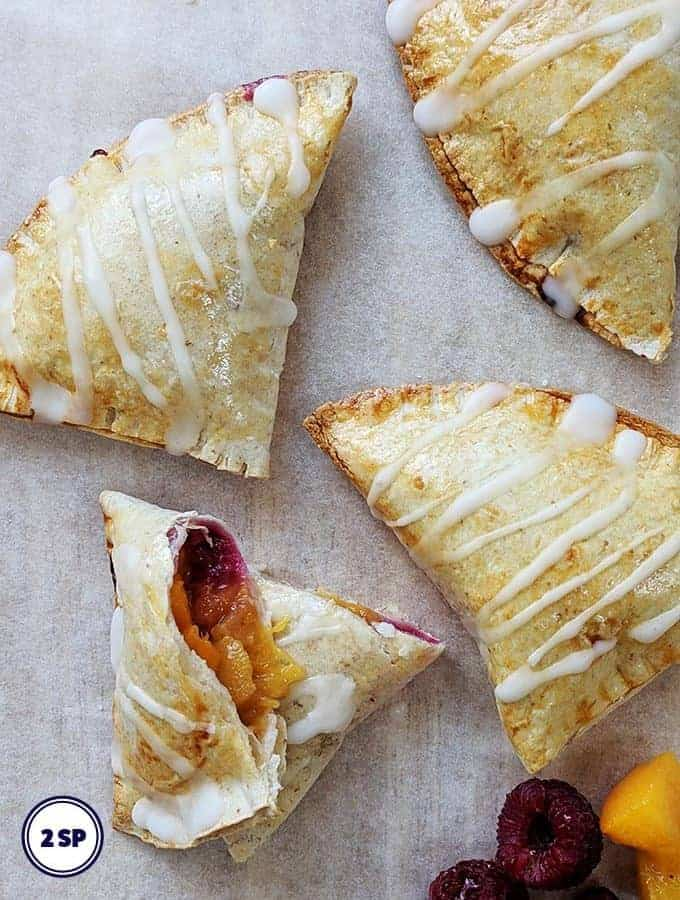 Peach pies on a sheet of parchment paper