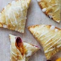 Peach pies on a sheet of baking parchment
