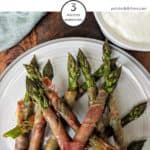 A plate of prosciutto wrapped asparagus tips on a white plate
