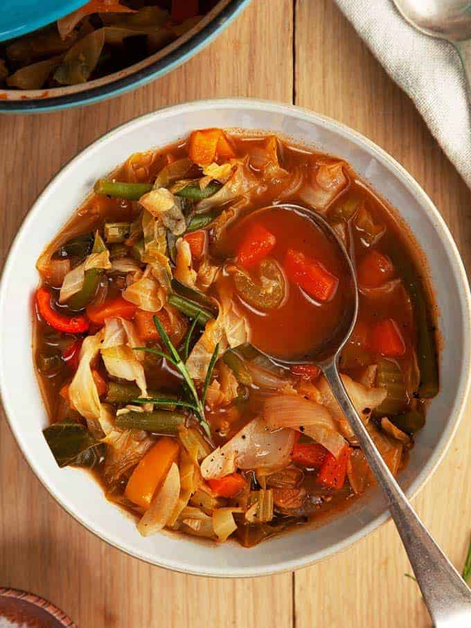 A bowl of zero smartpoint cabbage soup on a wooden table | weight watchers