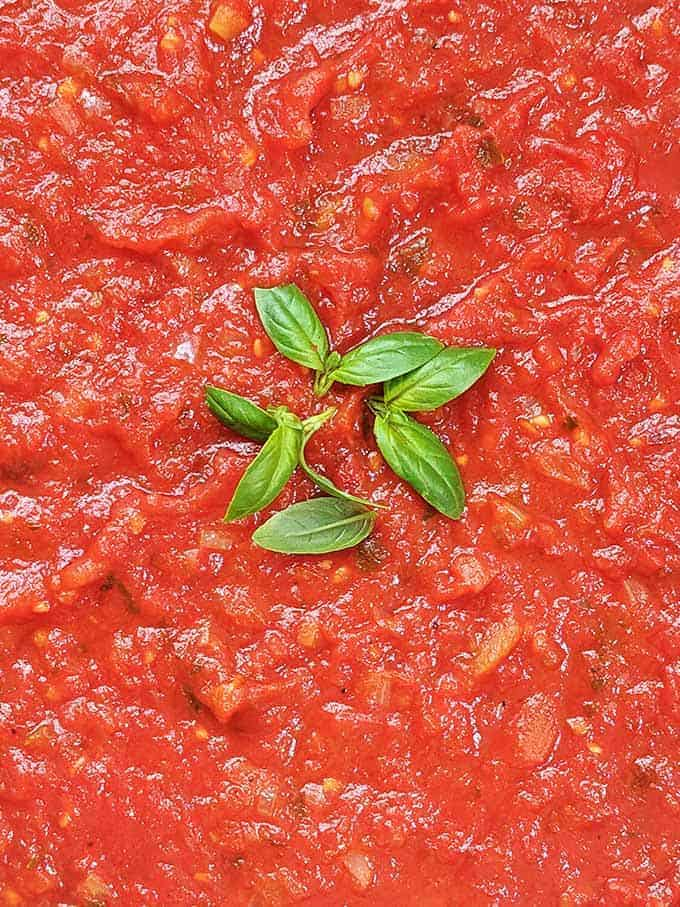 Bright red marinara sauce topped with green basil