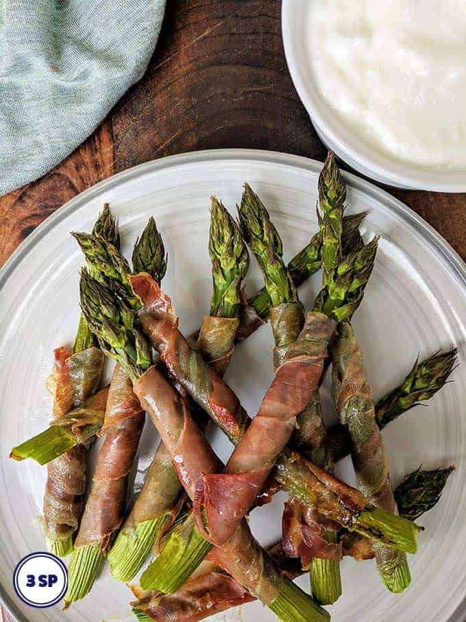 A white plate with prosciutto wrapped asparagus