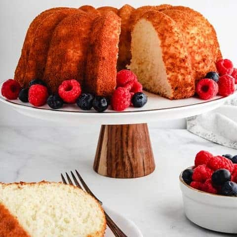 A pineapple angel food cake on a cake stand surrounded by berries