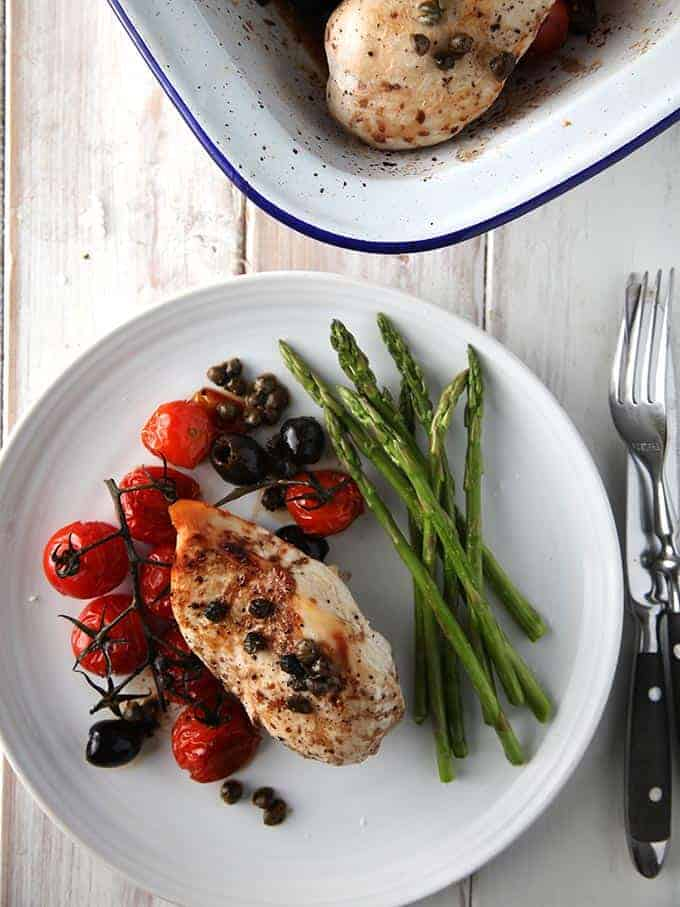 Balsamic chicken on a white plate served with asparagus spears