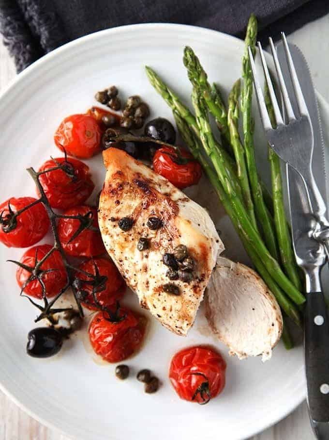 A plate of balsamic chicken on a white plate with asparagus