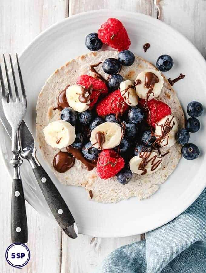 Berry Breakfast Taco on a white plate on a white table