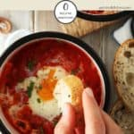 A dish of Shakshuka with bread being dipped into it