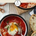 A white dish of shakshuka with a spoon in it