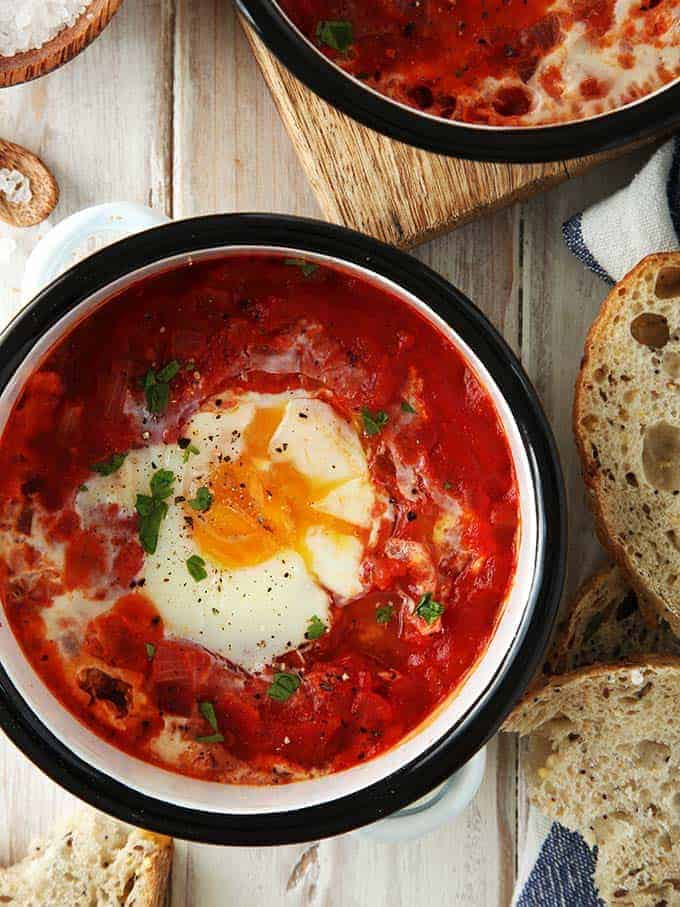 A dish of shakshuka on a white table with bread
