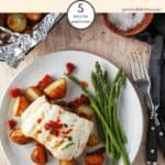 Baked cod & chorizo on a plate with new potatoes and asparagus