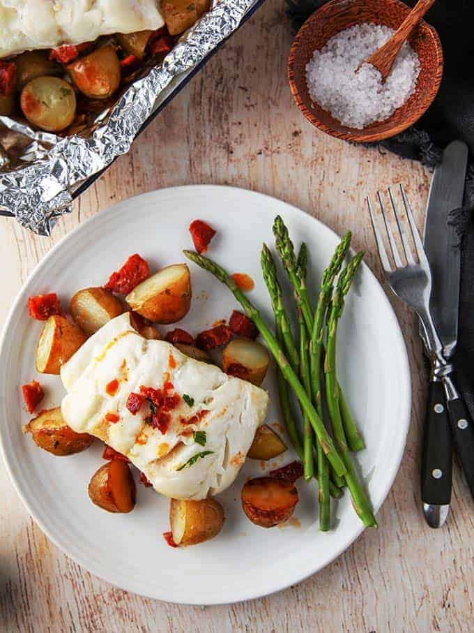 A plate of bake cod & chorizo with new potatoes on a wooden table
