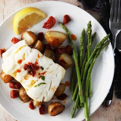 A close up picture of Cod & Chorizo with new potatoes and asparagus