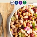 A bowl of colourful bean salad with wooden salad servers