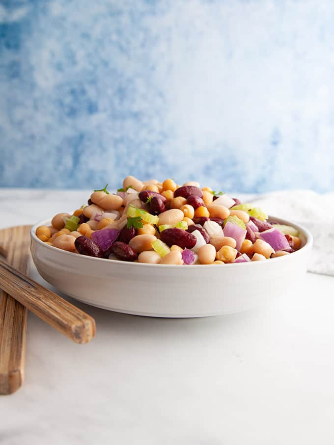 A white table with a bowl of three bean salad