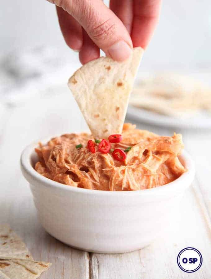 A chip being dipped into a bowl of buffalo chicken dip