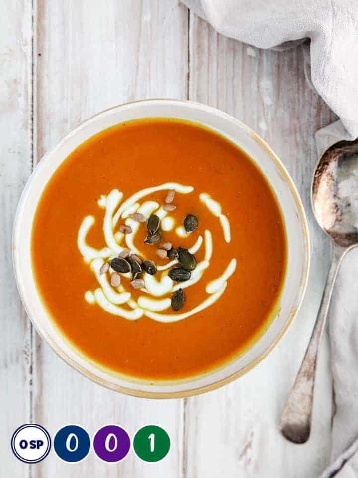 A bowl of orange soup on a white table