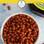 Some marmite chickpeas in a white bowl with a pot of marmite to the side
