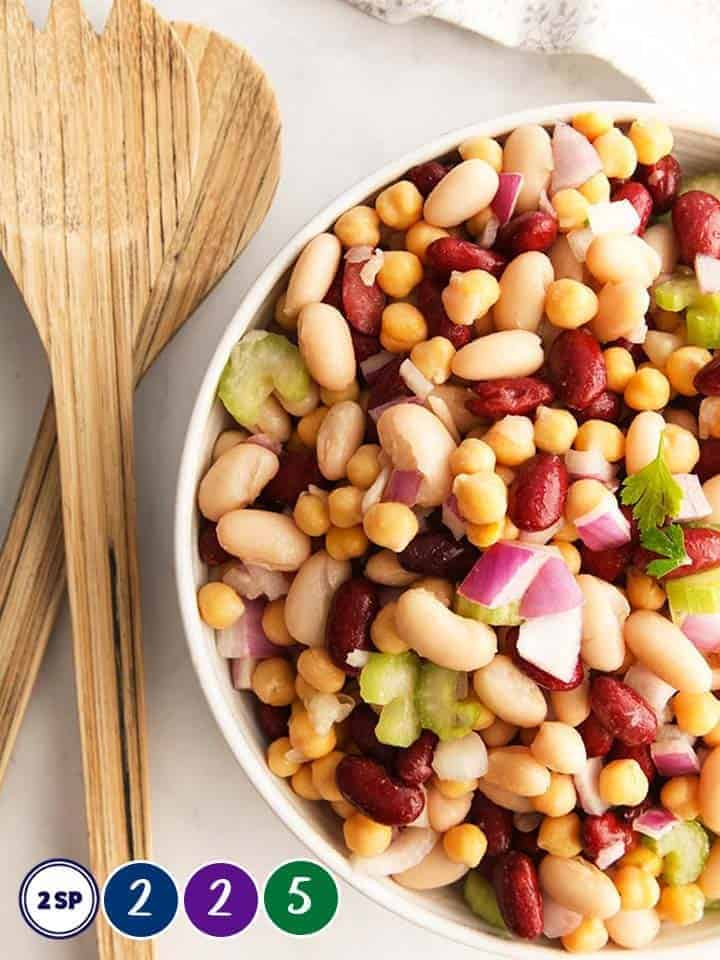 A bowl of bean salad with wooden salad servers