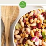 A bowl of three bean salad with a wooden serving spoon