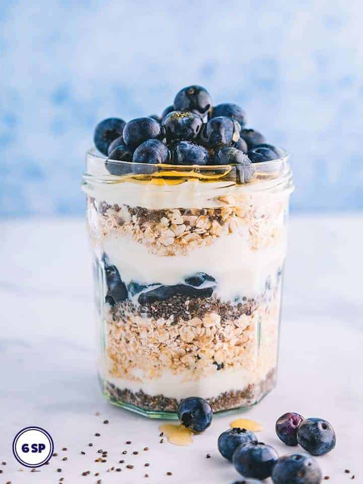A jar of overnight oats topped with blueberries