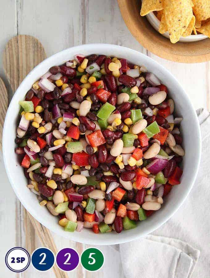 A white bowl of bean salad on a white table with salad servers