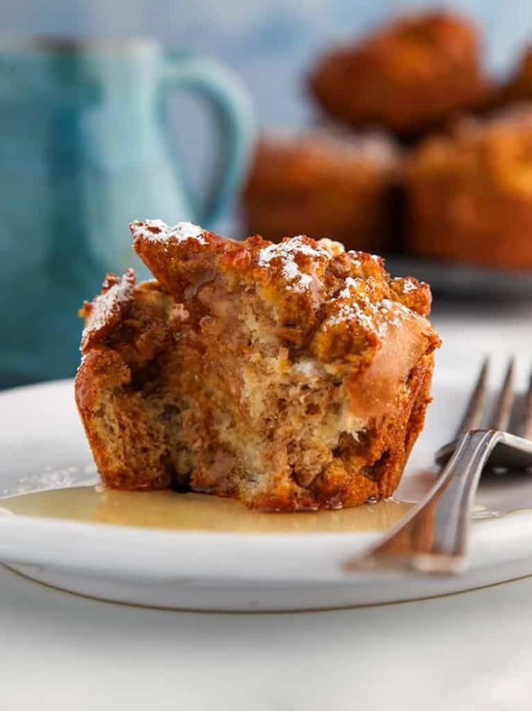 A pumpkin spiced french toast muffin with a fork on a white plate