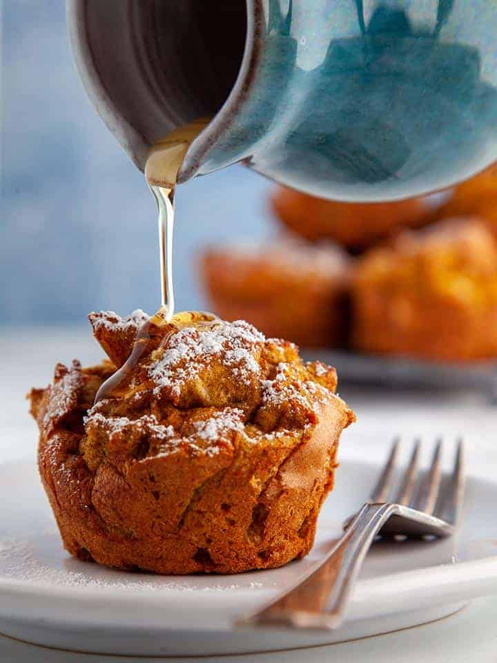 Syrup being poured over a pumpkin spiced french toast muffin