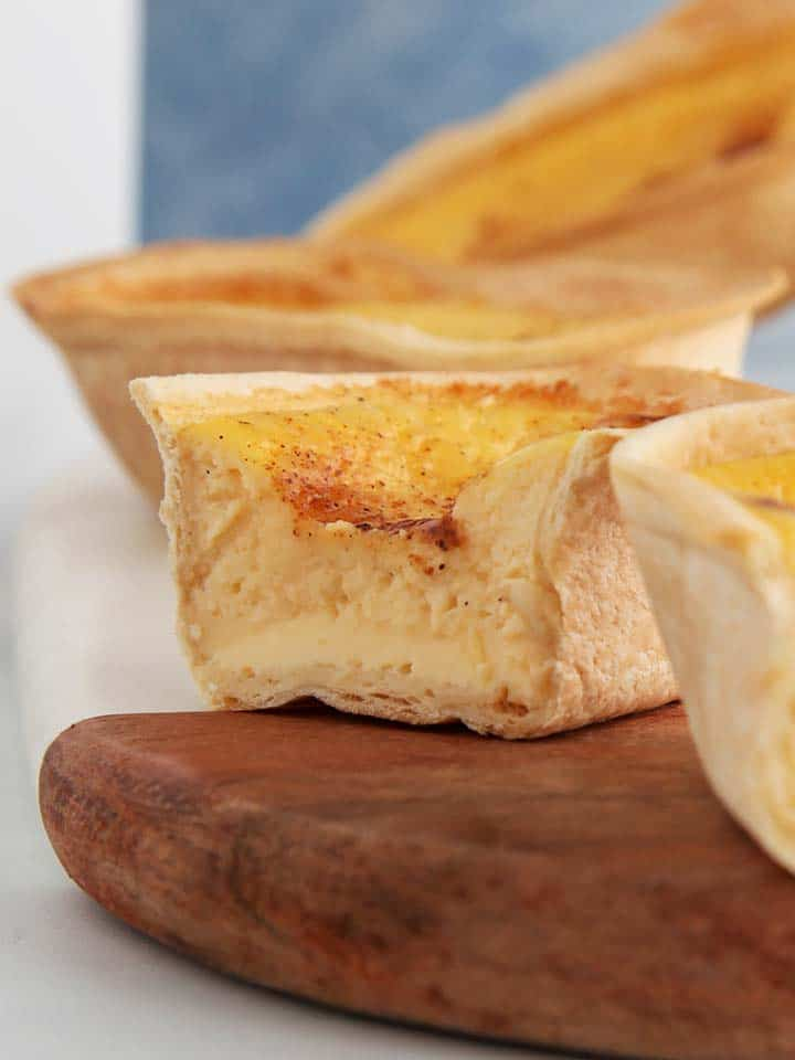 A close up picture of a custard tart on a wooden board