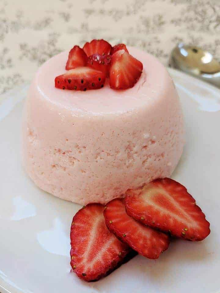 A pink fluff dessert on a white plate surrounded by strawberries