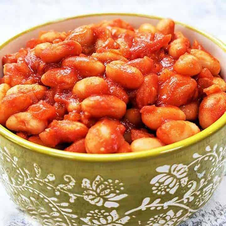 A green bowl full of red baked beans