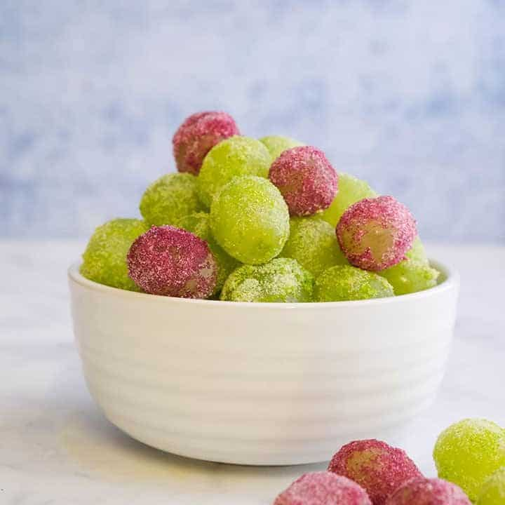 A bowl of grapes that are covered in jello crystals