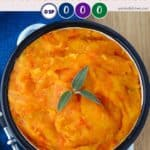 A dish of mashed carrots and rutabaga on a blue background