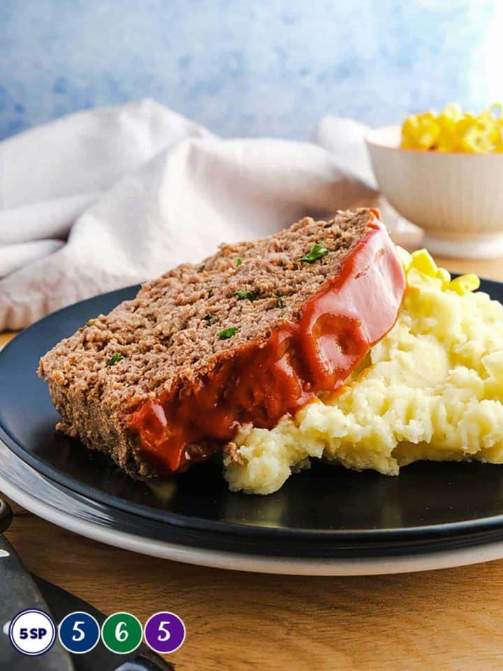 A black plate with a slice of meatloaf on mashed potato.