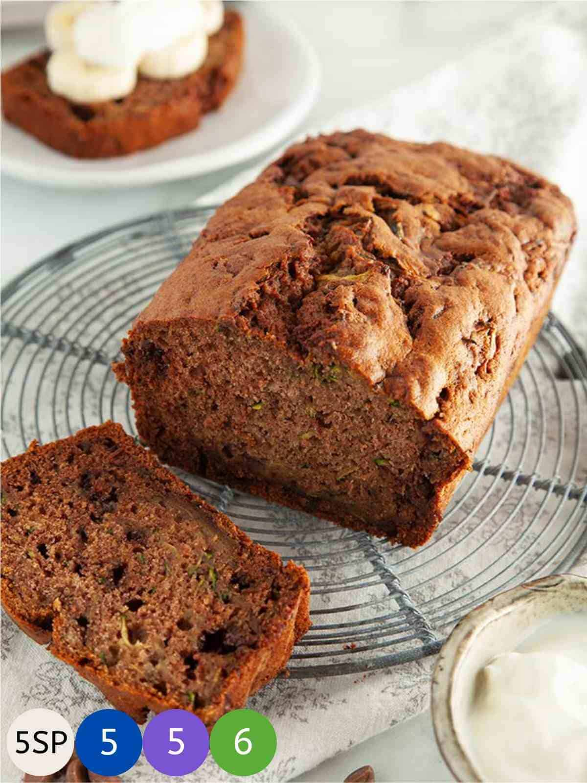 A chocolate chip zucchini bread loaf on a circular metal cooling rack