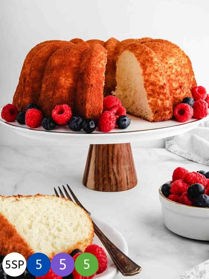 A Pineapple Angel Food cake on a white cake stand surrounded by raspberries and blueberries