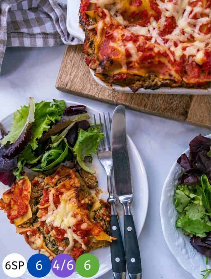 A white plate with some vegetable lasagna and salad