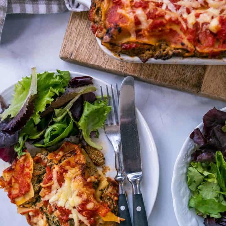 A white table with a dish of lasagna and a white plate with lasagna & salad