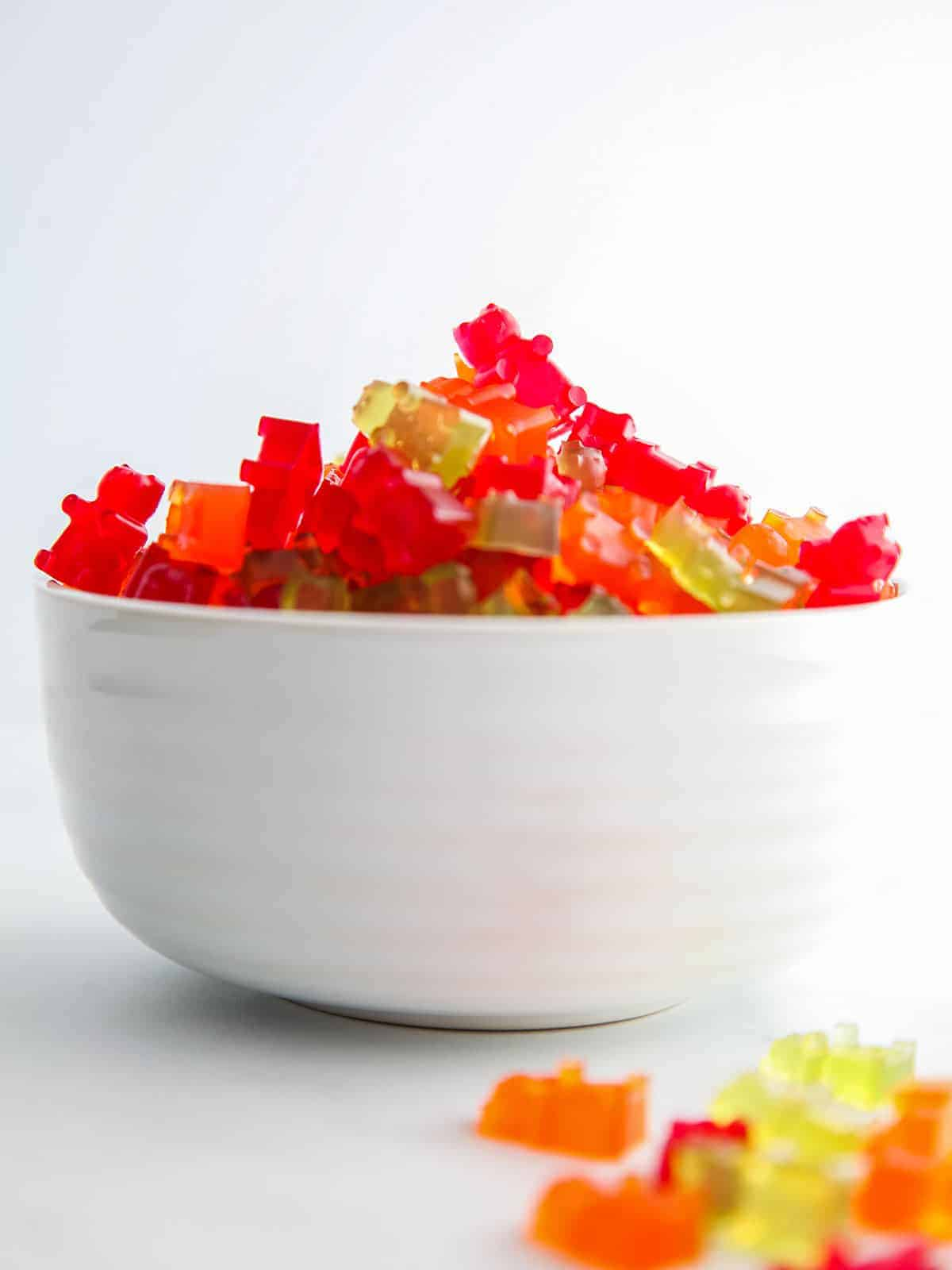 A white bowl of red, green and orange gummy bears