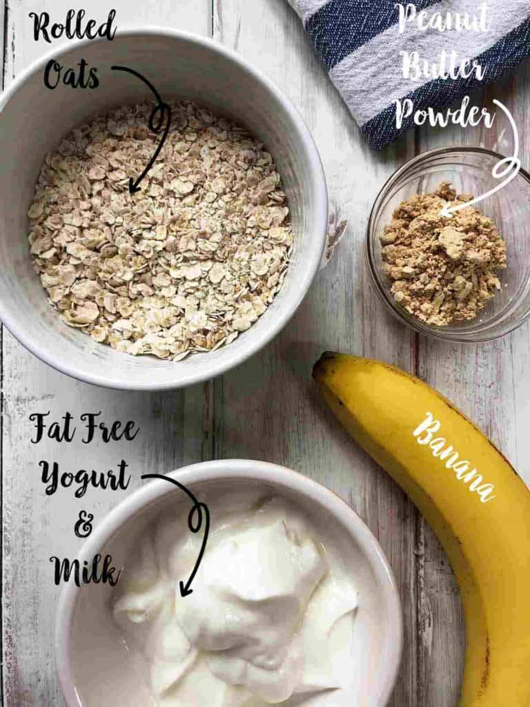 Bowls filled with yogurt, rolled oats and PB powder and a banana on a white table