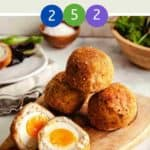 Four scotch eggs on a wooden board with one egg cut in half