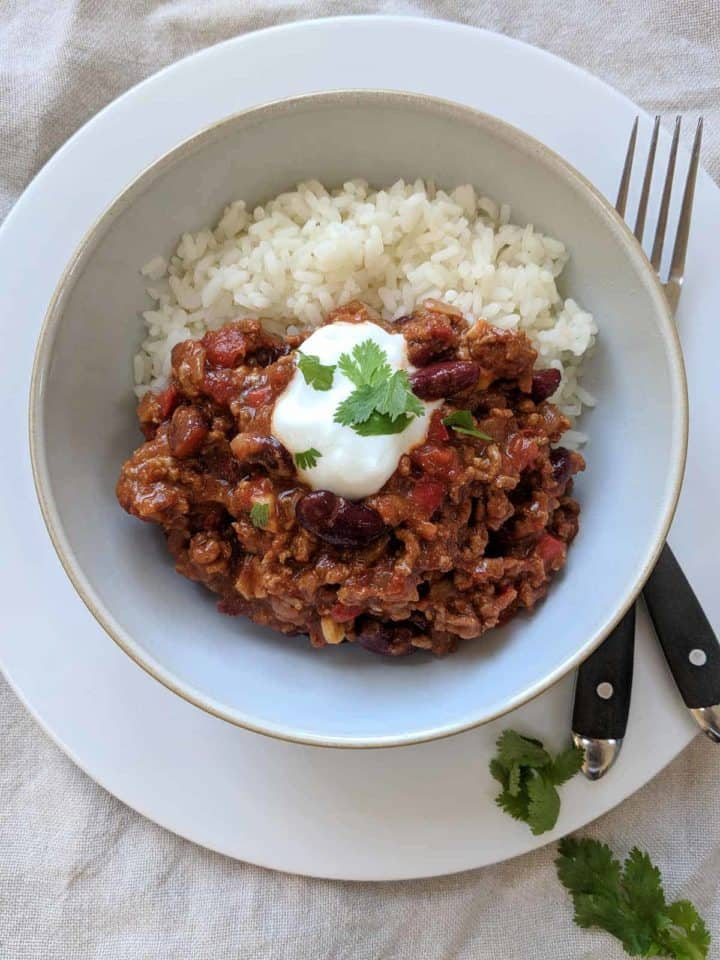 A white bowl of chili con carne and rice on a plate with a knife & fork and some herbs.