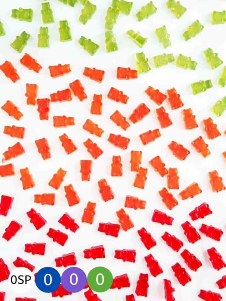 Red, green and orange gummy bears on a white table