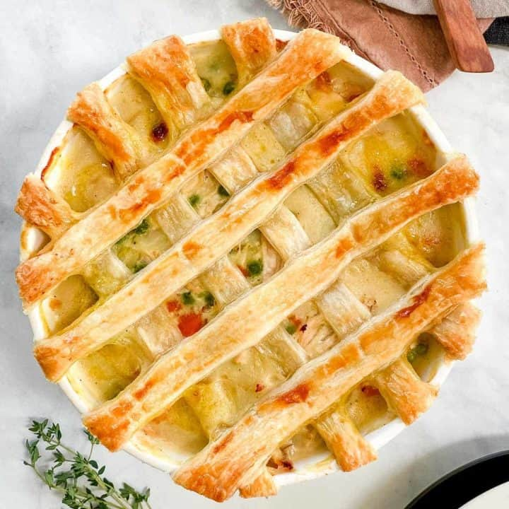A dish of chicken pot pie with a pastry latticed top and a sprig of thyme