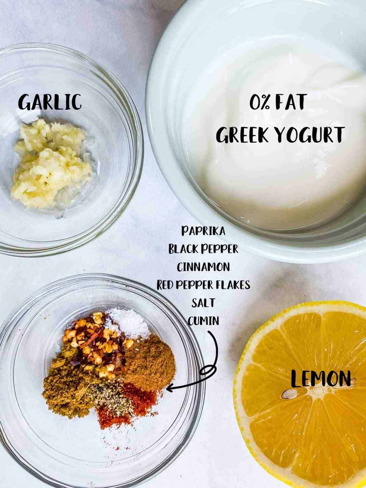 Small bowls of garlic, yogurt, and middle eastern spices and a lemon on a white table