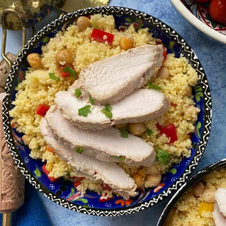 Sliced chicken on a bed of cous cous in a blue patterned bowl.