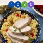 A decorative blue bowl full of couscous salad with sliced chicken on top