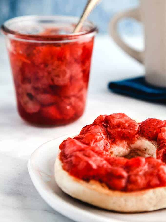 A glass jar full of strawberry jelly with a spoon sticking out and a bagel smothered with jelly infront on a white table.